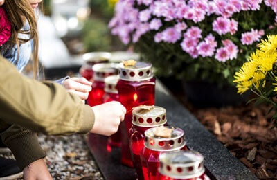 people lighting candles on grave